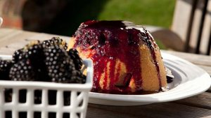 Steamed apple sponge pudding with blackberry sauce