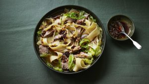 Wide noodles with lamb shank in aromatic broth